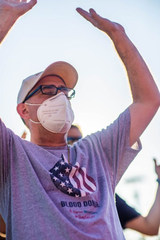anonymous man in respiratory mask standing with raised arms